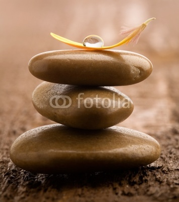 Pile of brown massage stones on wooden background